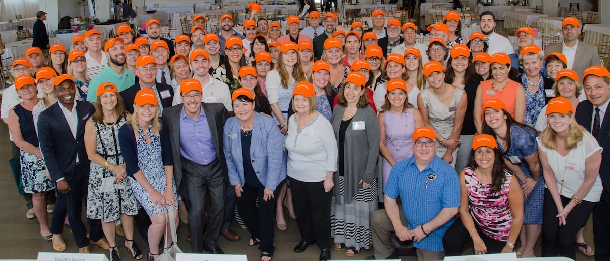 Large group of people wearing orange hats